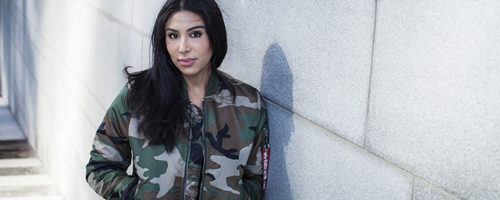 Melody Farshin stående mot vägg utomhus