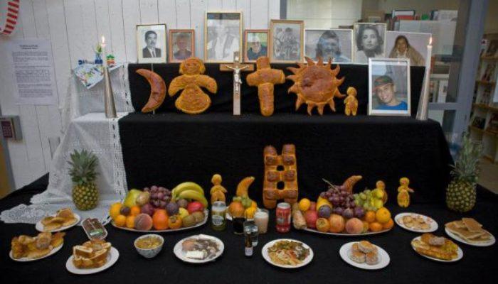 Uppdukat altarbord för firande av Todos Santos. Svart duk, frukter på fat, tatawawas och godsaker. Samt tända levande ljus och fotografier på döda anhöriga.
