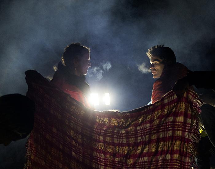 Två personer bakom en filt i nattmiljö. Foto av Angelica Harms